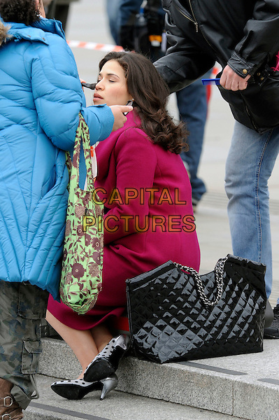 AMERICA FERRERA .Filming 'Ugly Betty' on location at The Millenium Bridge, London, England, UK, 5th April 2010. .filmset film set full length pink red coat black bag purse sitting polka dot shoes white make-up stylist.CAP/IA.©Ian Allis/Capital Pictures.