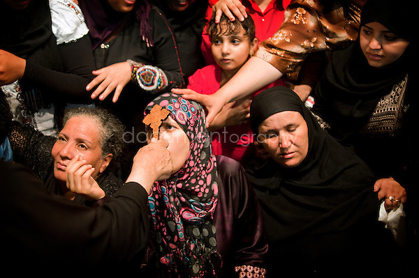 Dozens of Muslims and Copts women are scrambling to approach Father Samaan, to kiss his hand as a sign of respect,  to ask a blessing or an exorcism.<br />