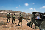 Israeli soldiers in a tent near the unauthorized Israeli settler-outpost of Adei Ad, West Bank, securing the area between it and neighboring Palestinian villages.