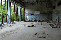 Looting in the gymnasium - somebody have tried to steal the wooden floor - of the swimming hall &quot;Azure&quot; in Pripyat.<br /> Pripyat was built 1970 as a modern city for personnel at the Chernobyl Nuclear Power Plant, located some kilometers south. After the nuclear disaster at reactor 4 on April 26 1986, the town's 48.000 inhabitants was evacuated to other parts of the country. Pripiat is today a radioactive ghost town. The whole area is contamined with nuclear material, the half-life of plutonium-239 is more than 24.000 years.<br /> Pripyat, Ukraine.<br /> August 2008.