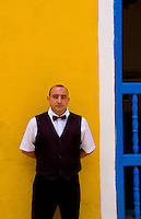 Waiter against bright yellow wall of building of the old colonial city of Trinidad in Cuba