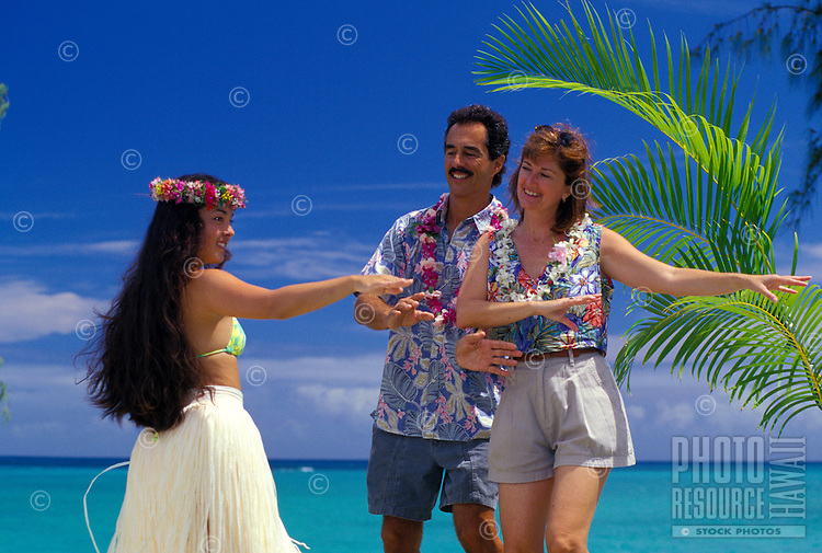 Tourist couple learning hula at the beach