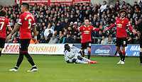 SWANSEA, WALES - FEBRUARY 21: Bafetimbi Gomis of Swansea is injured on the ground while Wayne Rooney (C) and Marouane Fellaini of Manchester protest to the referee during the Barclays Premier League match between Swansea City and Manchester United at Liberty Stadium on February 21, 2015 in Swansea, Wales.