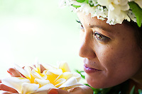 A beautiful young Hawaiian woman smelling some fragrant plumerias