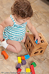 13 month old baby girl at home on floor playing with toy geometric shape sorter fitting piece in hold vertical