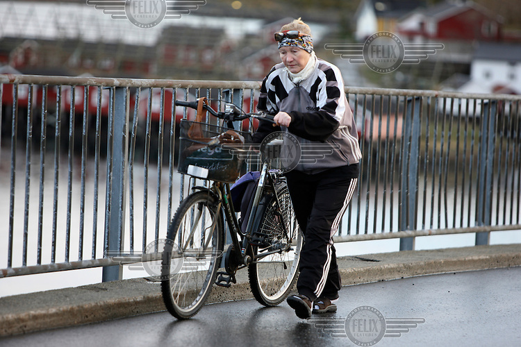 A woman walks with her bicycle on a bridge in Svolvaer.