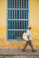 Senior man walking along a city street past a wooden grilled window, Trinidad, Cuba.