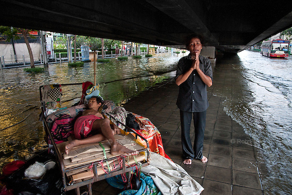 A woman and her sick husband shelter under a bridge in northern Bangkok. She seemed to be Cambodian and, I am guessing, one of the many migrant workers who were left with no jobs and little support when their workplaces flooded.<br />