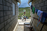 "A woman carries water past houses in a model resettlement village constructed by the Lutheran World Federation in Gressier, Haiti. The settlement houses 150 families who were left homeless by the 2010 earthquake, and represents an intentional effort to ""build back better,"" creating a sustainable and democratic community."