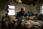 Snow Leopard (Panthera uncia) veterinarian, John Ochsenreiter, checking immobilization drugs while ranger, Temirlan Baktygul, and biologist, Rahim Kulenbek, relax, Sarychat-Ertash Strict Nature Reserve, Tien Shan Mountains, eastern Kyrgyzstan
