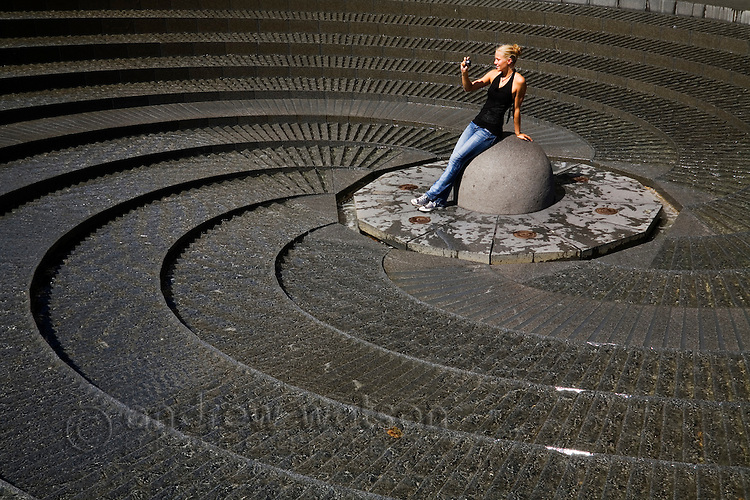 A woman photographs the quirky spiral fountain at Darling Harbour.  Sydney, New South Wales, AUSTRALIA
