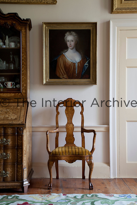 A Dutch marquetry armchair stands below a portrait in the drawing room