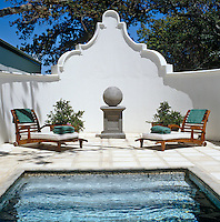A pair of sun loungers on an enclosed terrace with steps leading down into the swimming pool in the foreground