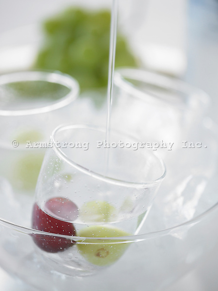 Glasses of vodka with green and red grapes, in a large bowl of ice