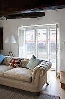 In the living room of the converted Victorian canalside warehouse large French windows open onto views of the water