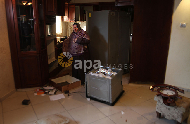 A Palestinian woman inspects the damages at her house after an Israeli military operation, at Balata refugee camp naer in the West Bank city of Nablus January 21, 2015. Israeli forces launched a major detention campaign in the northern West Bank refugee camps of Balata and Askar in Nablus district overnight, Palestinian security sources said. Photo by Nedal Eshtayah