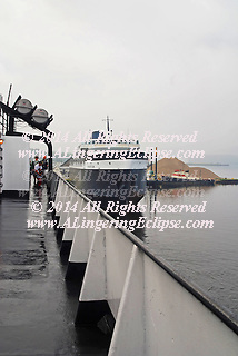 Shoot the Day: Lake Michigan Car Ferry, Historic Badger Vintage Rail, vehicle, passenger Ferry Ship on Lake Michigan in an early morning crossing on July 20, 2008 from Ludington MI to Manitowoc, WI.  Families, Grandparents, Parents and Children enjoy the trip together as an exciting 4 hour adventure relaxing and saving gasoline in difficult times!  Shown here, after a morning rainstorm, the SS Badger departs the dock for its journey westward against a backdrop of a moored tugboat and sandpile.