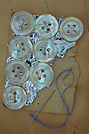Eight mother-of-pearl buttons attached to silvered display card lying with sewing needle and blue cotton thread