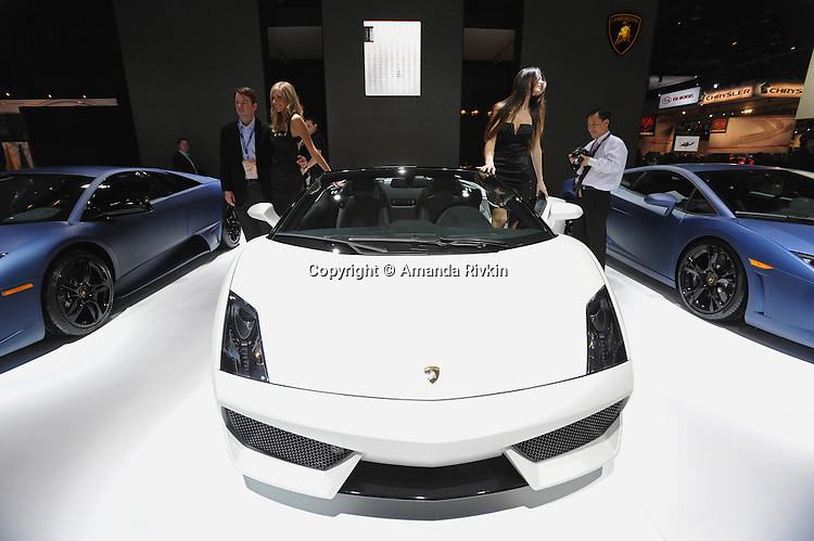 Car girls pose beside the 2009 Lamborghini Gallardo LP 560-4 Spyder at the Detroit Auto Show in Detroit, Michigan on January 11, 2009.