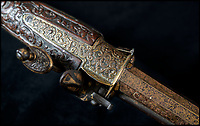 BNPS.co.uk (01202) 558833<br /> Pic: PhilYeomans/BNPS<br /> <br /> Ornate gold etching on the muskets lock and barrel.<br /> <br /> Stunning artefacts from Indian hero Tipu Sultan's fateful last stand have been rediscovered by the family of an East India Company Major who took part in the famous battle that ended his reign.<br /> <br /> And now Major Thomas Hart's lucky descendents are likely to become overnight millionaires after retrieving the historic items from their dusty attic.<br /> <br /> The fascinating treasures were taken from Tipu's captured fortress of Seringapatam in the wake of his defeat by British forces led by a young Duke of Wellington in 1799.<br /> <br /> The cache of ornate gold arms and personal effects even include's the battle damaged musket the Sultan used in his fatal last stand against the expanding British Empire in India.<br /> <br /> Tipu was last seen on the battlements of the fortress firing his hunting musket at the advancing British and after the fierce encounter his body was found bearing many wounds, including a musket ball shot above his right eye.<br /> <br /> The rediscovered musket, complete with battle damaged bayonet, has the distinctive tiger stripe pattern unique to the self styled Tiger of Mysore own weapons - and tellingly there is also shot damage to the lock and stock that may have been caused by the musket ball that finished him off.<br /> <br /> Also included in the sale are four ornate gold-encrusted sword's bearing the mark of Haider Ali Khan, Tipu's father and the previous ruler of independent Mysore, along with a solid gold &lsquo;betel casket&rsquo; complete with three 220 year old nuts still inside.<br /> <br /> The war booty was brought back to Britain by Major Thomas Hart of the British East India Company following the fourth and final Anglo-Mysore war.<br /> <br /> They have been passed down through the family ever since and now belong to a couple who have kept them wrapped in newspaper in the dusty attic of their semi-detached home for years.