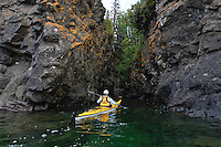 A sea kayaker paddles the rugged Lake Superior shoreline of Isle Royale National Park in Michigan.