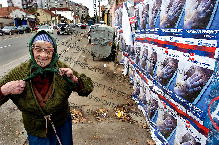 "An elderly woman passes by Democratic party of serbia ""what is said has been done"" posters  after constitutional referendum, Belgrade November 1 , 2006. Serbia voted  a two-day referendum on a new constitution that enshrines the breakaway province of Kosovo as an ""inalienable"" part of Serbia. photo: Pedja Milosavljevic"