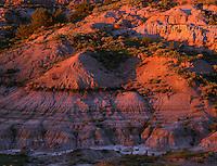69NDTR_02 - USA, North Dakota, Theodore Roosevelt National Park, Sunset light defines eroded sedimentary hillside near Boicourt Overlook in the South Unit.