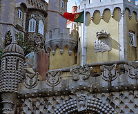 The royal coat of arms on the tower above the entrance and behind it a profusion of architectural styles and details that make up the palace