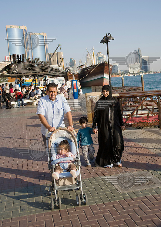 A family walking along the embankment alongside  Dubai Creek.