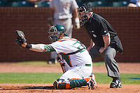 Miami Hurricanes catcher Yasmani Grandal #24 sets a target as home plate umpire Nelson Graham looks on at the 2010 ACC Baseball Tournament at NewBridge Bank Park May 26, 2010, in Greensboro, North Carolina.  The Hurricanes defeated the Seminoles 9-3.  Photo by Brian Westerholt / Four Seam Images