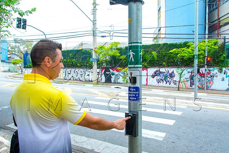Pedestre apertando botão de semáforo para travessia, São Paulo - SP, 09/2016. Uso de imagem autorizado
