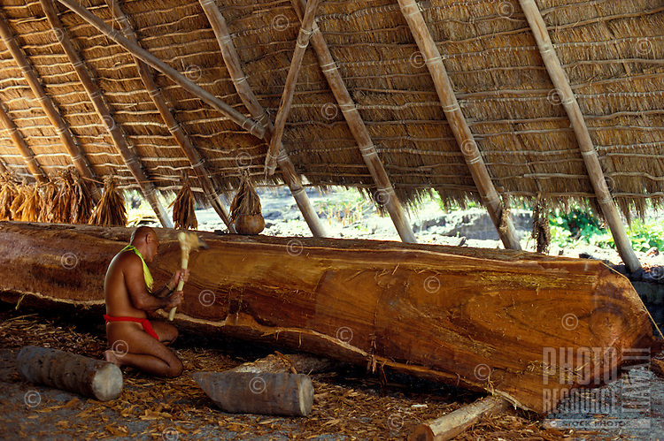 Hawaiian man wearing malo, carving contemporary Hawaiian sailing canoe under a thatched hale at Puuhonua o Honaunau National Historic Park in Kona, Big Island of Hawaii