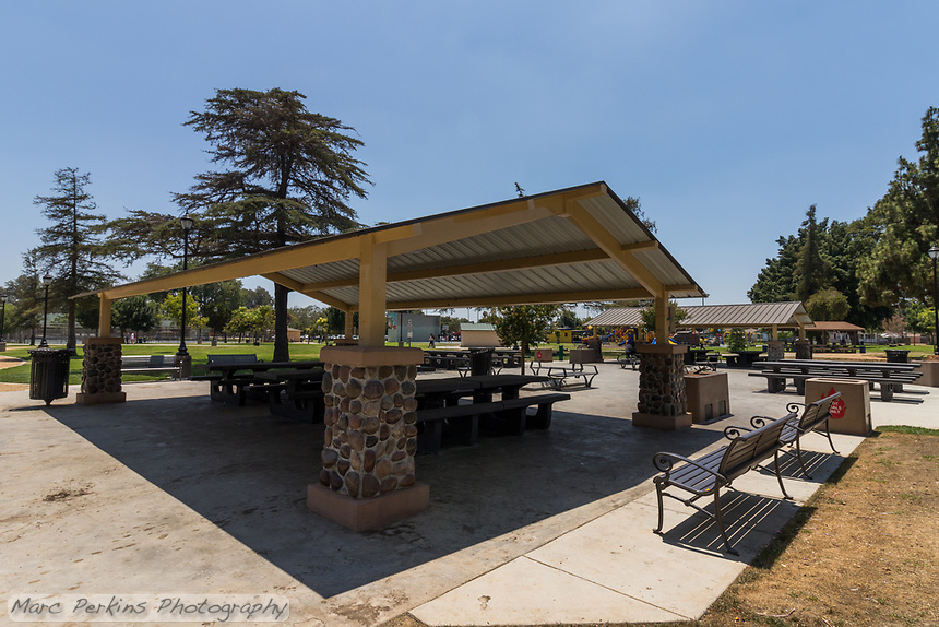 One the new picnic shelters installed at South Gate Park during the recent renovation, showing shaded picnic tables and benches next to benches and other picnic tables that are in the sun.