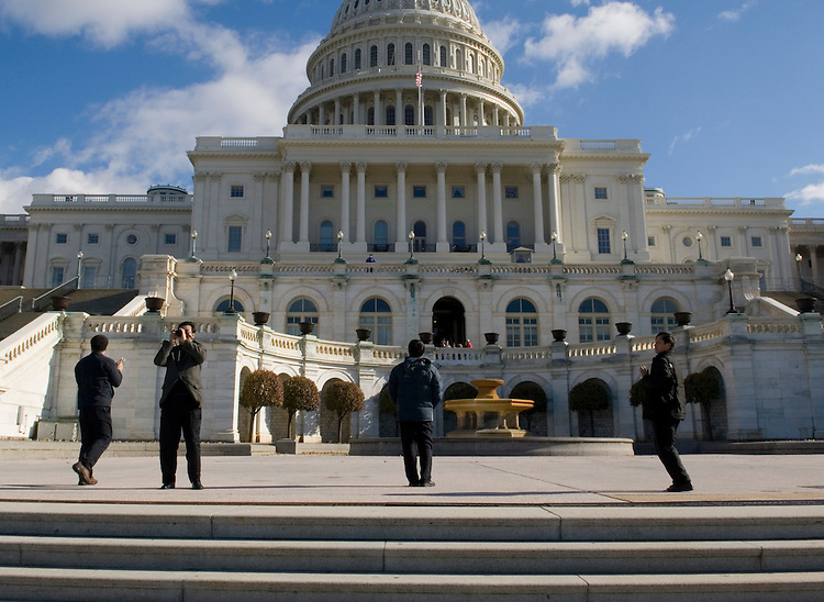 Tourists take photos on the West Front of the U.S. Capitol as high chilly winds blew through Washington on Monday, Dec. 3, 2007.