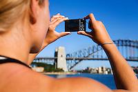 A woman photographs the Sydney Harbour Bridge.  Sydney backpacker.  Sydney, New South Wales, AUSTRALIA