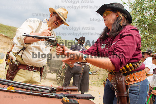 Judge (L) checks the weapon loaded by a participant during the Cowboy Action Shooting European Championship in Dabas, Hungary on August 11, 2012. ATTILA VOLGYI