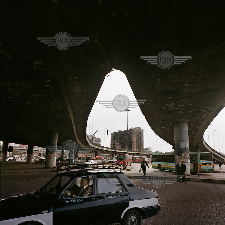 A taxi passing beneath the 6th October Bridge, in the background is the headquarters of former President Mubarak's party, the PND. The building was badly burned, during anti-government protests on the 28 January 2011.