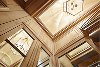 A view from below of wood panelling with built in mirrors.