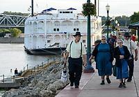USA, Iowa, Dubuque, river Mississippi, Amish People walking on riverfront , behind steam boat american duchess / Amische, Amischen sind eine täuferisch-protestantische Glaubensgemeinschaft
