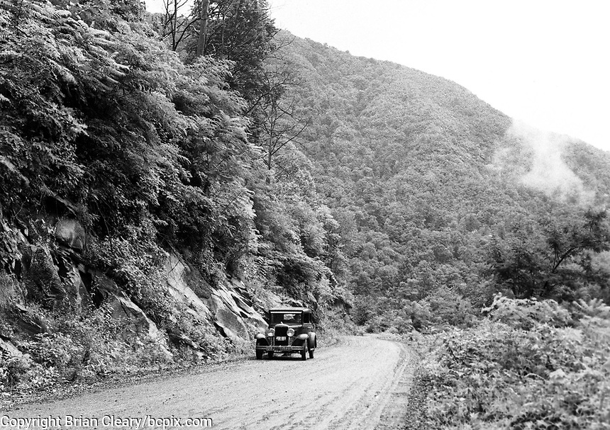 An old-fashioned car drives on the Indian Gap Road, Smokey Mountains, NC, in 1930's America.  (photo by bcpix.com)