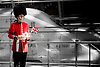 Beefeater with afternoon tea tray in front of black and white background of the EuroStar at Kings Cross Station.