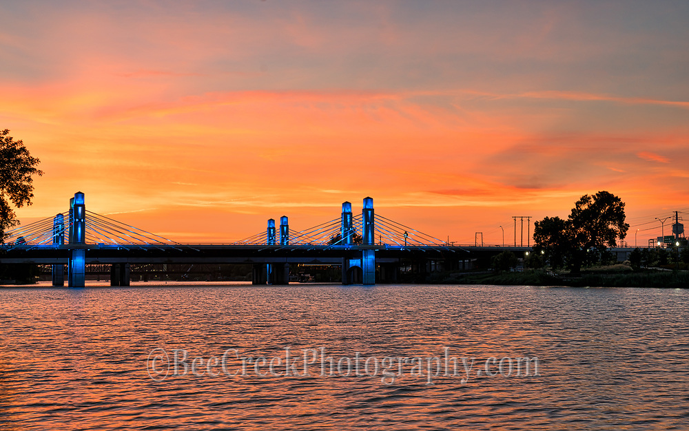 Took this from another section along the brazos river with this incredible orange sky at sunset which was perfect backdrop for the blue lights of this stay bridge across the Brazos River in Waco on this night. This stay bridge was recently completed on IH35 or the Jack Kultgen Freeway as it is called through Waco.The highway through Waco is called the Jack Kultgen Freeway named after a civic leader and philanthropist who did a lot of work for charities in Waco for six decades. This stay bridge also runs along side of the Baylor Bears stadium which it was design to ease traffic through the area during games.  Also Baylor University has control of the led lights on this stay bridge so for special events they can be change to Baylors Bear colors.