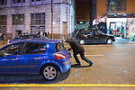 © Joel Goodman - 07973 332324 . Manchester , UK . 05/04/2015 . A man comes to the aid of the driver of a broken down car , which has been causing a road blockage on Withy Grove in Central Manchester . Revellers on a Saturday night out during the Easter Bank Holiday weekend . Photo credit : Joel Goodman