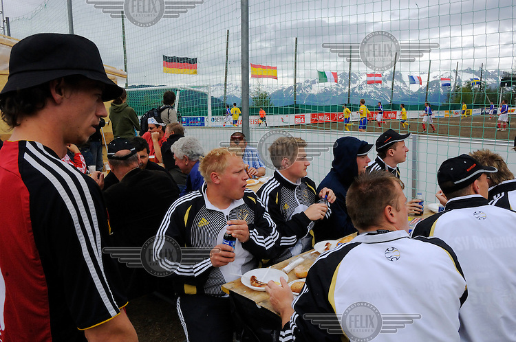 The German team eat pre-match bratwurst while a match is in progress behind them at the other official Euro 2008 football tournament: the European Championship of Mountain Villages. The hosts FC Gspon drew with Italians FC Piedemulera 3 - 3 in a nail-biting match. The tournament was held at their summer training ground, standing at 2008 metres above sea-level,  and surrounded by 4000 metre alpine peaks. It is the highest football pitch in Europe, and reachable only by cable car, or a long walk. Amateur league teams from eight countries took part.