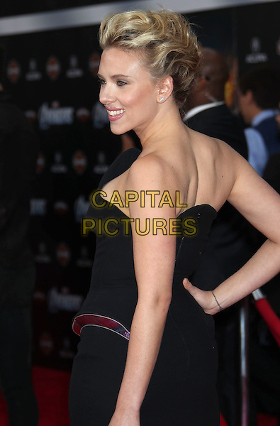 """Scarlett Johansson.""""Marvel's The Avengers"""" World Premiere held at the El Capitan Theatre, Hollywood, California, USA..April 11th, 2012.half length dress hand on hip black strapless profile back behind rear.CAP/ADM/RE.©Russ Elliot/AdMedia/Capital Pictures."""