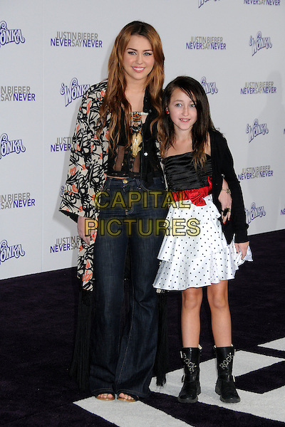 "MILEY CYRUS & NOAH CYRUS .""Justin Bieber: Never Say Never"" Los Angeles Premiere held at Nokia Theater L.A. Live, Los Angeles, California, USA, .8th February 2011..full length black jacket tassels fringe bed jacket kimono  print orange wide leg flares flared jeans sandals open toe sisters siblings family red bow polka dot white tiered dress boots .CAP/ADM/BP.©Byron Purvis/AdMedia/Capital Pictures."