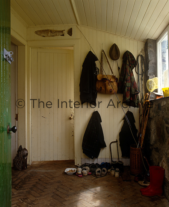The back door to the fishing lodge opens into a utility room, home to an assortment of jackets, fishing rods and footwear