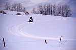 Snowmobiler Enjoying Riding through Fresh Snow in a Pasture in New Hampshire