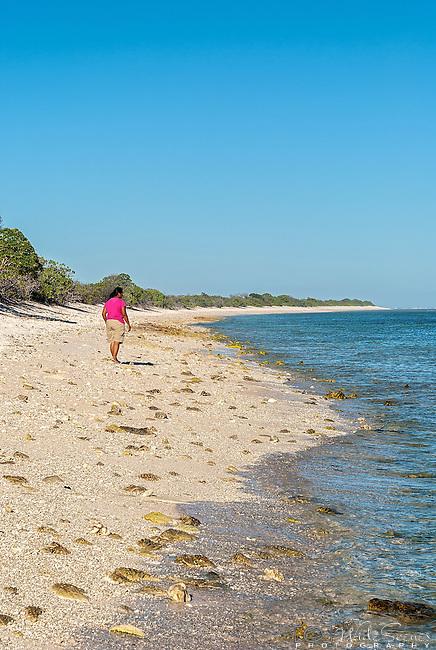 An i-Kiribati woman walks along a remote beach on the island of Kiritimati, Kiribati.