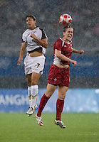 USWNT midfielder (7) Shannon Boxx goes up for a header with  Canadian midfielder (6) Sophie Schmidt while playing at Shanghai Stadium.  The US defeated Canada, 2-1, in extra time and advanced to the semifinals during the 2008 Beijing Olympics in Shanghai, China.